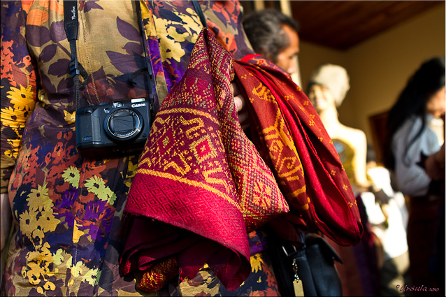 Close-up woman with a camera, with colourful silks over her arm