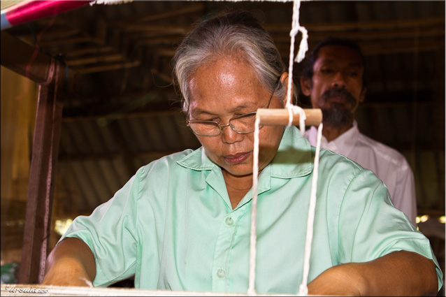 Elderly Thai Woman at the Head of a two-story silk loom