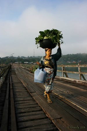 Mon woman with basket of vegetables on her head walking on a wooden Bridge