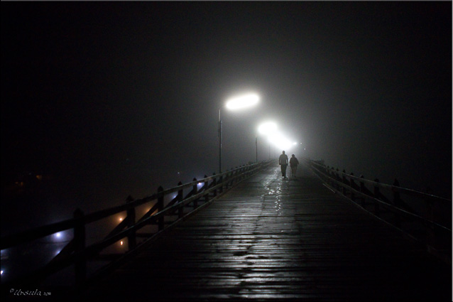 People on a wooden bridge in the dark