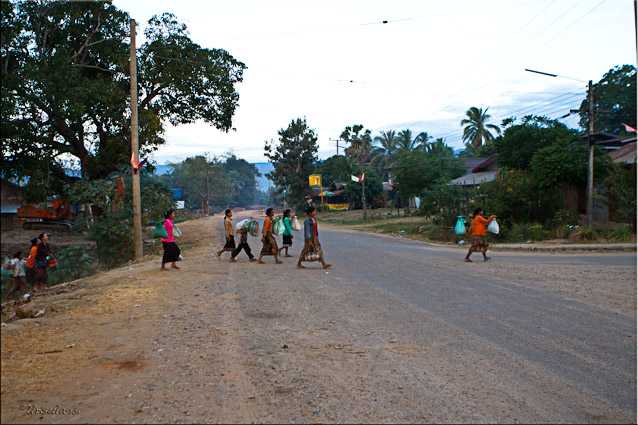 Lao people crossing a dusty road in Attapeu