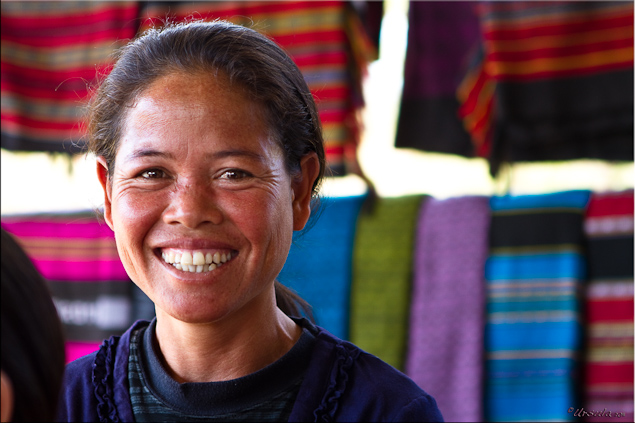 Portrait: Taliang woman and colourful cotton weaving (Laos)
