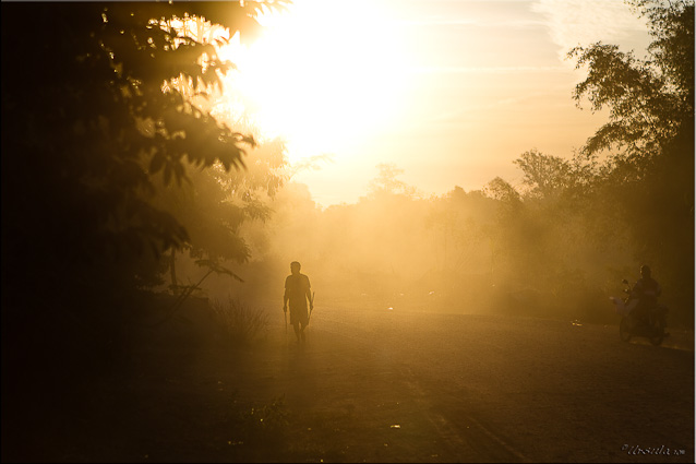 Man walking on dusty road at suntise, Attapeau, Laos