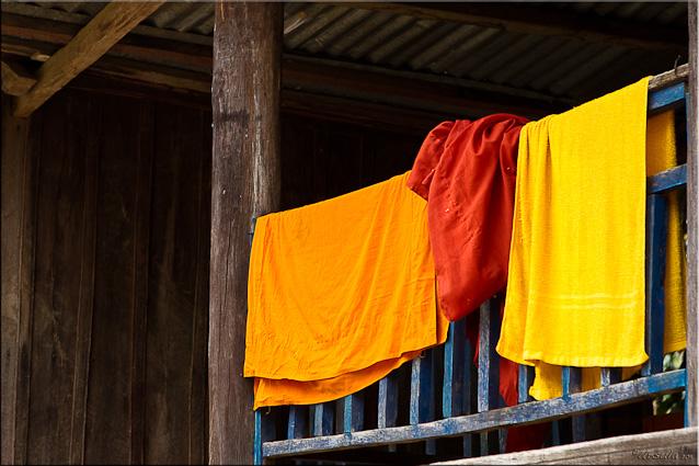 Orange and saffron cloths on a balcony rail, Attapeu, Laos