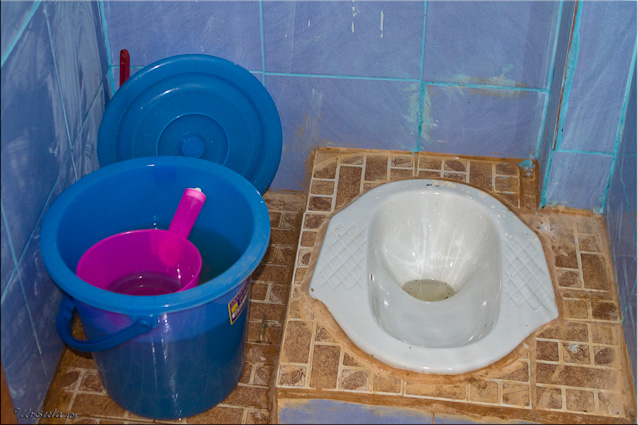 Squat toilet with blue water pail