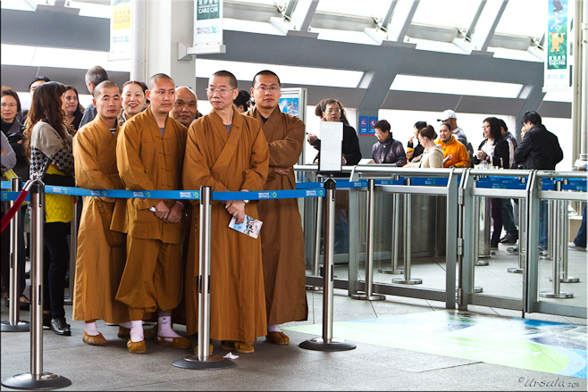 Monks in brown robes waiting in line