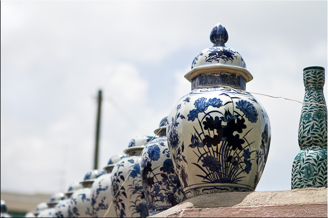 Large blue and white ceramic pots against a blue and white sky
