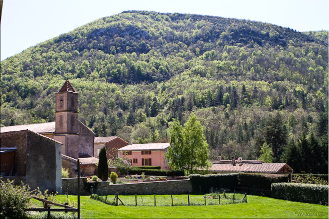 View of Sougraine church and village against a forested mountain