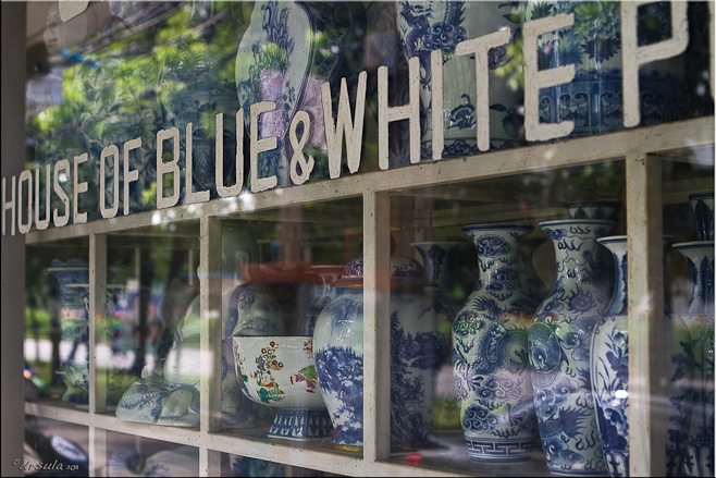 """""""House of Blue and White Pottery"""" Shop front, with shelves of pots behind glass"""
