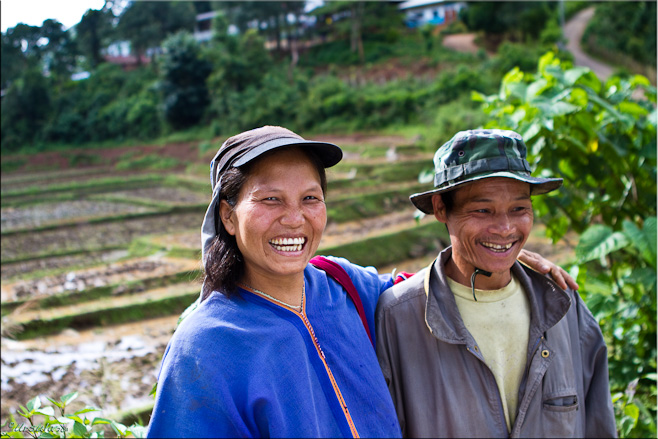 Karen man and woman in front of fields