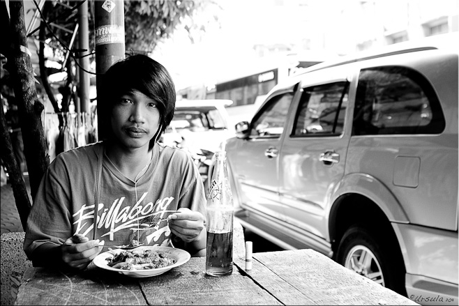 B&W Young thai man eating noodles