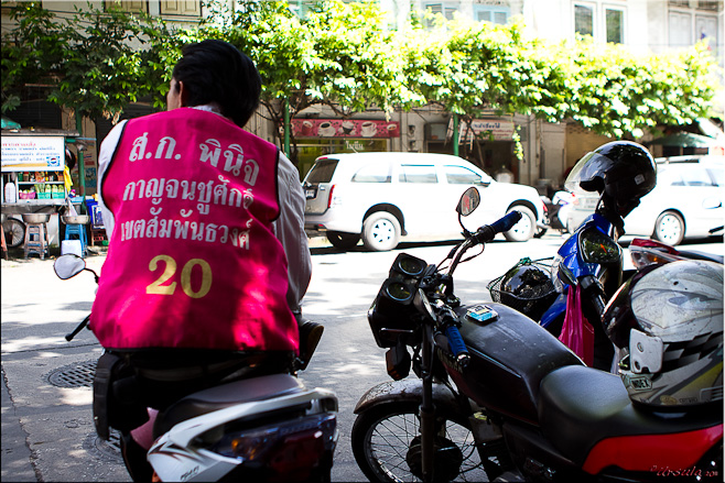 Back of a thai male in a bright pink motorcycle taxi vest