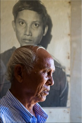 Portrait: Mr Chum Mey, survivor of S-21 Tuol Sleng, in front of a picture of a victim