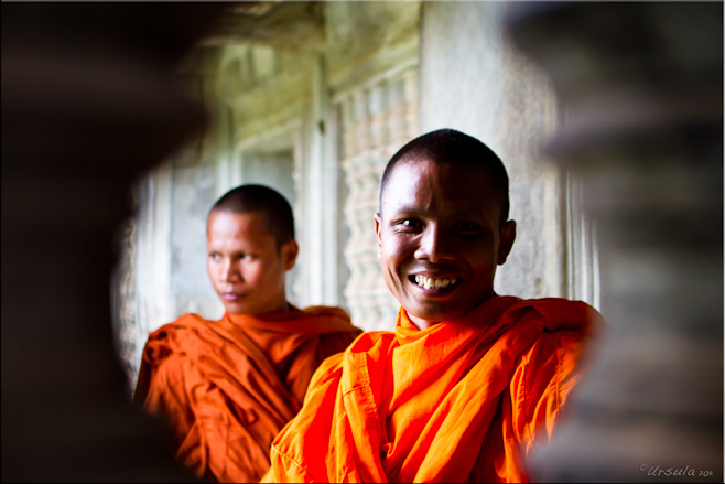Portrait: Two Theravada monks seen through the balusters of an Angkor Wat corridor
