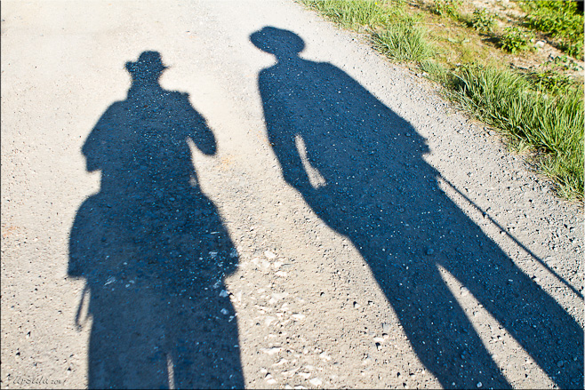 Shadows of two people on a gravel road