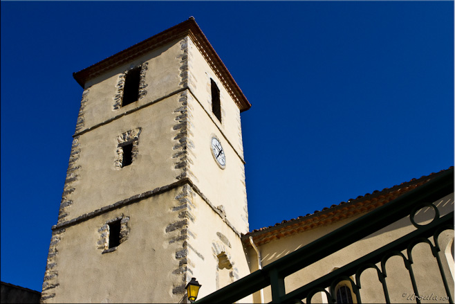 Modern church clock and bell tower against a blue sky