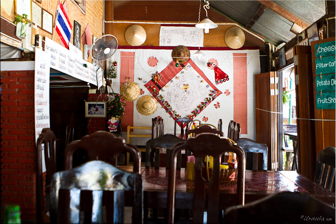Inside a cafe: Chairs, quilting and wicker-work  on the walls