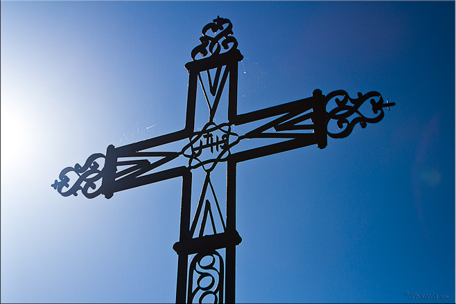 Sun angling into a large black wrought iron cross