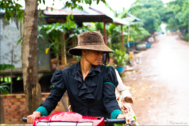 Khmer woman in a brown hat on a red motorcycle