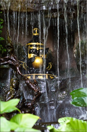 Gold-painted black figurine of a Thai hermit, set in a waterfall