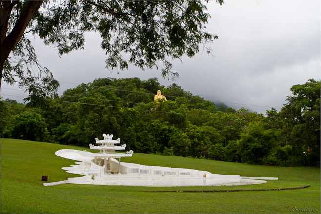 An elaborate white chinese grave, set into a sculptured green lawn - a golden Chinese buddha on the green hill behind