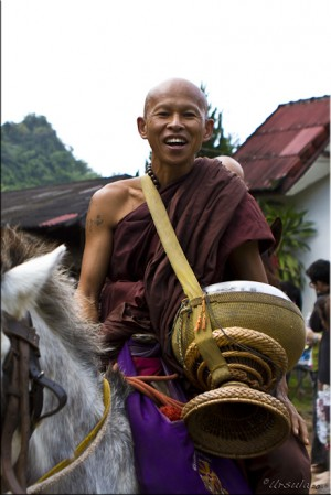 Smiling monk astride a white horse, with a large gold begging bowl.
