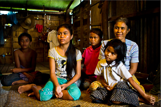 Khmer mother, three daughters and son seated on a grass mat in a bamboo house.