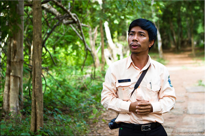 Portrait: Serious-looking Khmer man in long-sleeved shirt in front of jungle.