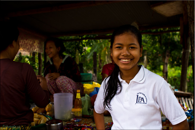 Portrait: Adolescent Khmer girl in her white school uniform polo shirt.