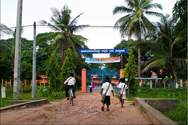Children in school uniform walk and cycle to the gates of Sandan School, Cambodia
