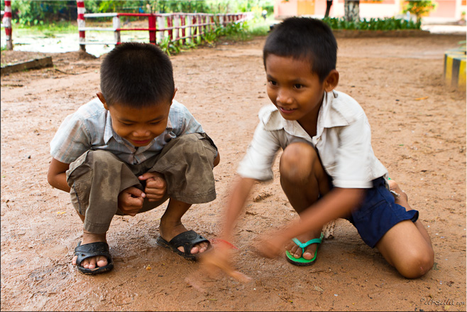 Two khmer boys squatting on dirt, playing marbles