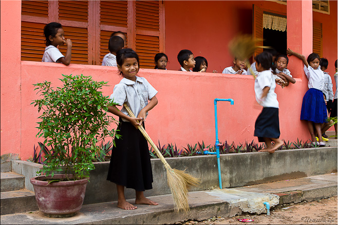 Young khmer girl in school uniform with a straw broom.
