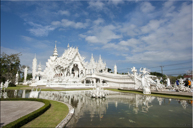 Wide angle view of the white temple: Wat Rong Khun set in waters an gardens.