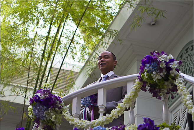 Thai male in a dress suit on a balcony draped in flower arrangements.