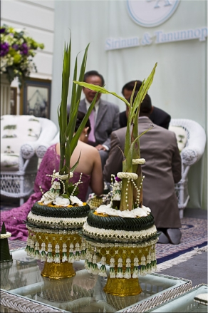 Foreground: Two elaborate bai sri (Thai floral decorations). Background: Newlyweds and their parents.