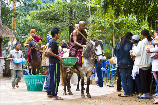 Monks on horseback collect food, water and other goods from supporters.
