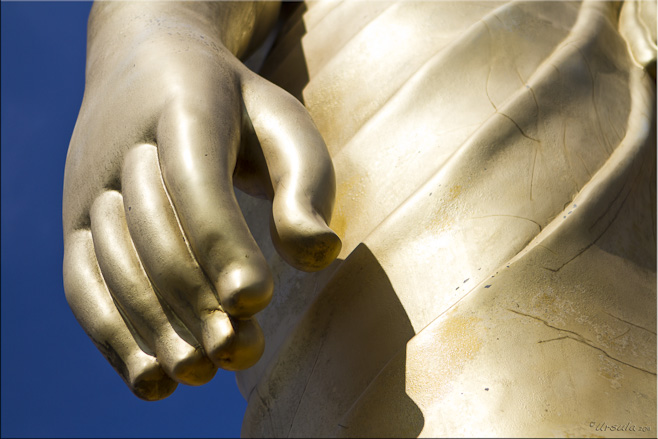 Large hand at the side of a golden buddha statue.