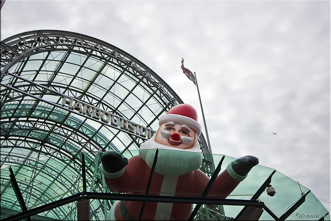 Large blow-up santa on a glass roof: Harbourside Darling Harbour, Sydney