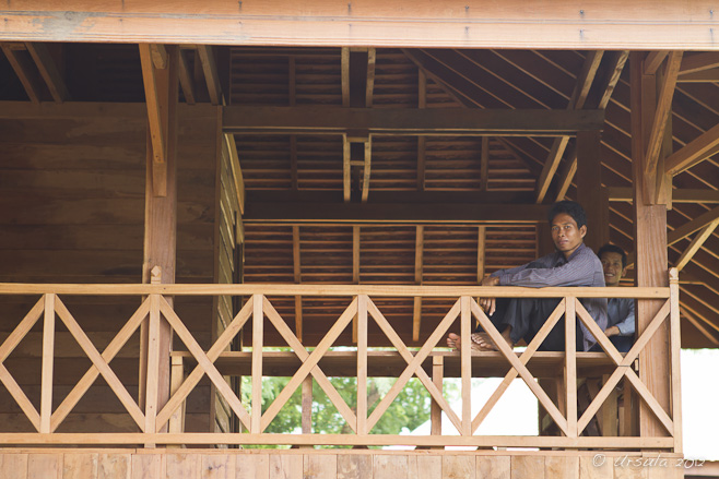 A khmer man sitting on timber framing on the balcony of an unfinished wooden building.