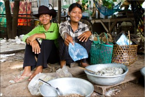 Two khmer women sitting behind metal bowls of floured meat and fish in a simple market.