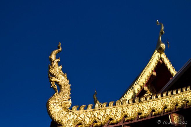 Golden garuda-shaped chofah (light tassel), the decorative temple roof trim, against a blue sky.
