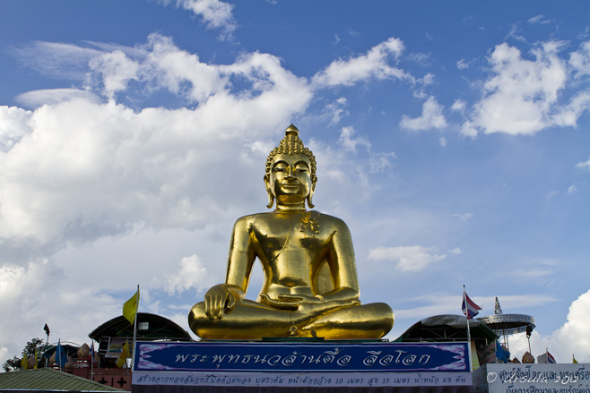 Seated Golden Buddha against a blue sky with white clouds.