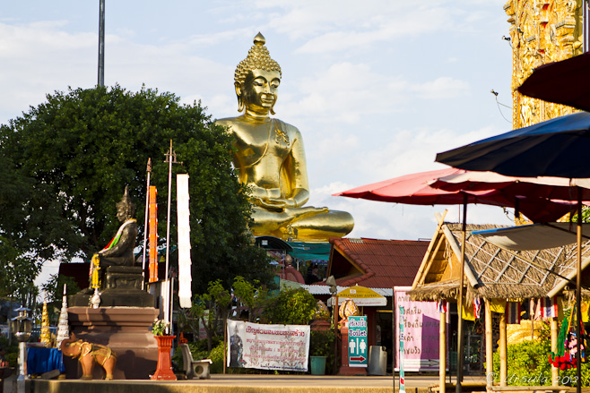 Golden Buddha amid signage, umbrellas, and other images