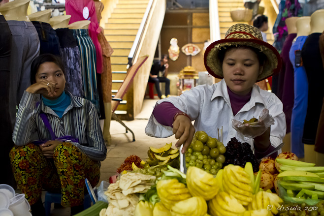 Khmer woman in a straw hat selling cut fruit as another woman looks on.