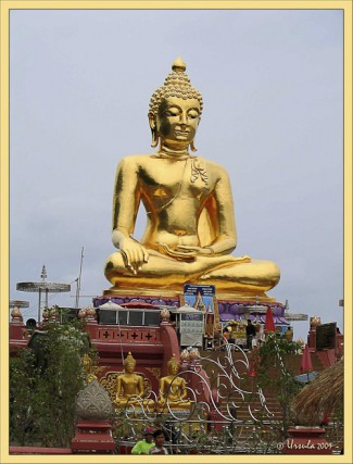 Seated golden Buddha against a gray sky