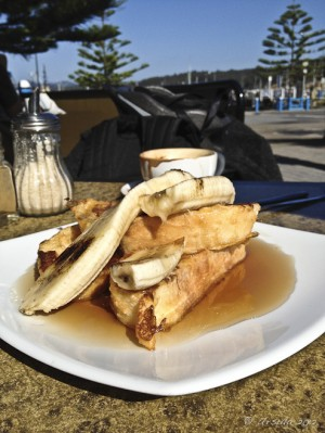 Piled thick French toast with syrup and banana on an outdoor table.