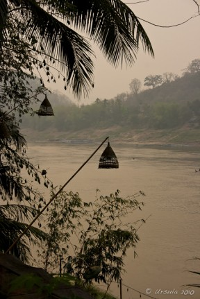 Evening light on the muddy Mekong River, Bamboo lamps in the foreground