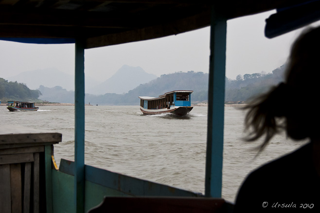 View of a traditional wooden Lao river boat, from another. Mekong River and hills in the background.