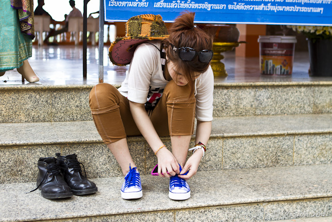 Young wombs sitting on temple steps, removing her running shoes.