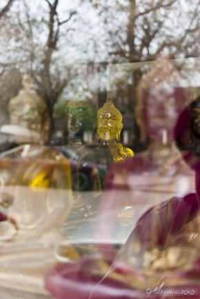 Reflections of trees and coloured glass Buddha images, shop window: Luang Prabang